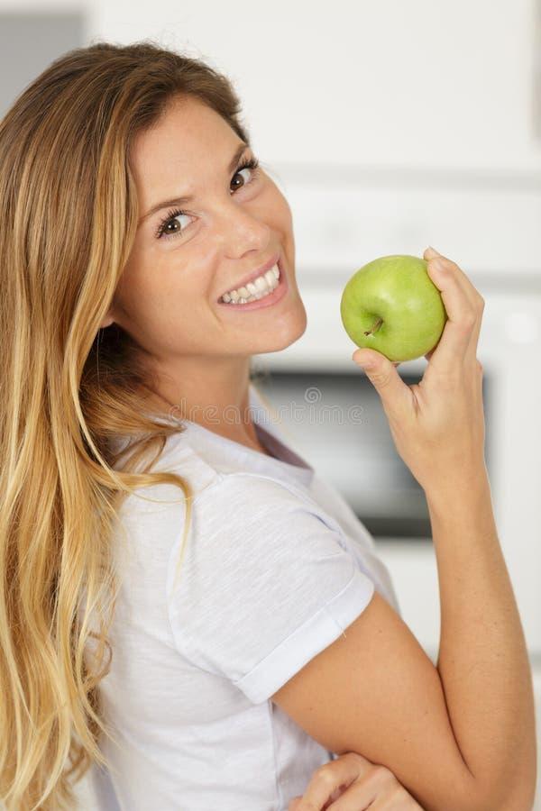 Mujer feliz que muerde la manzana verde imágenes de archivo libres de regalías