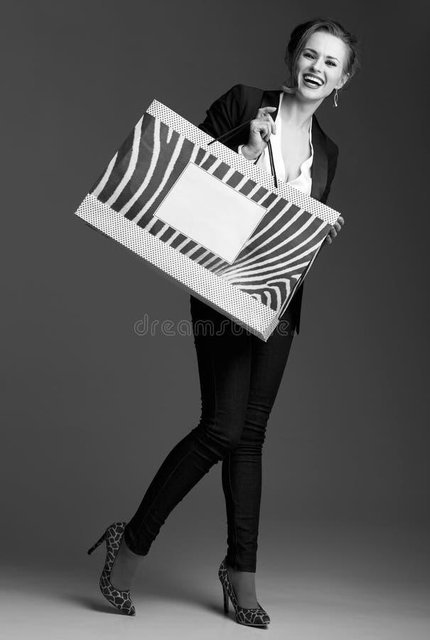 Mujer feliz que muestra el panier grande contra fondo gris imagen de archivo libre de regalías