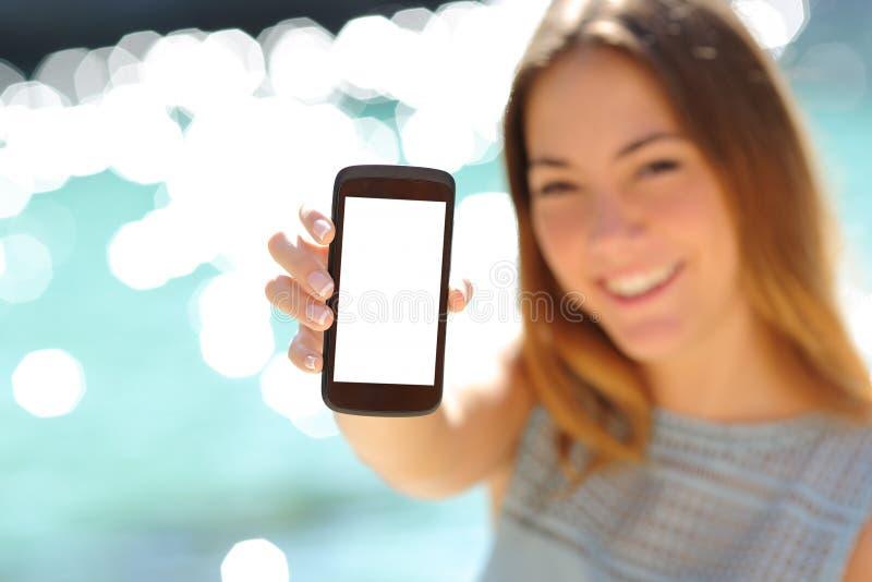 Mujer feliz que muestra un smartphone en blanco en la playa imagen de archivo