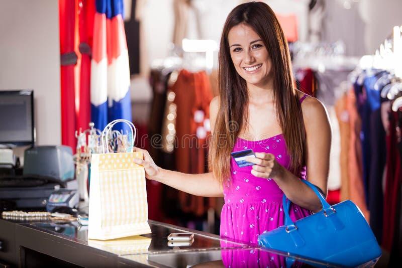 Mujer feliz que paga con la tarjeta de crédito fotos de archivo libres de regalías