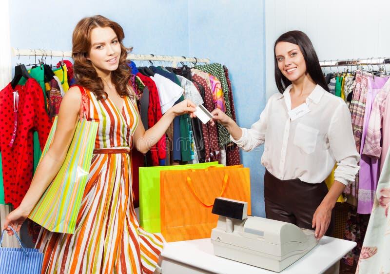Mujer feliz que paga con la tarjeta de crédito compra fotografía de archivo