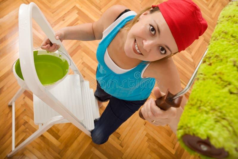 Mujer feliz que pinta el techo en una escala foto de archivo