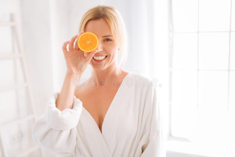Mujer feliz que presenta con el pedazo de naranja imágenes de archivo libres de regalías