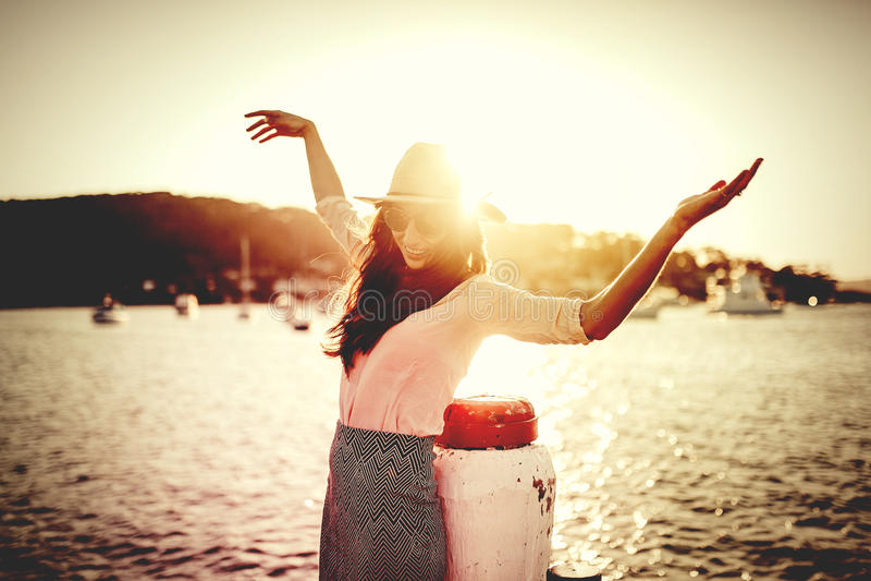 Mujer feliz que presenta delante del océano con los brazos para arriba Luz filtrada hermosa de la puesta del sol fotos de archivo