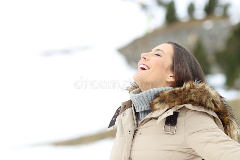 Mujer feliz que respira el aire fresco en vacaciones de invierno imagen de archivo