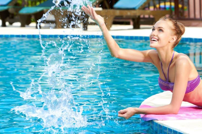 Mujer feliz que salpica el agua en piscina imagen de for Piscina que pierde agua