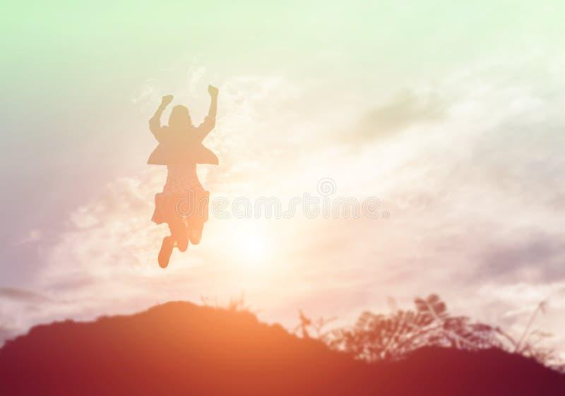 Mujer feliz que salta contra puesta del sol hermosa Libertad, concepto del disfrute imagen de archivo