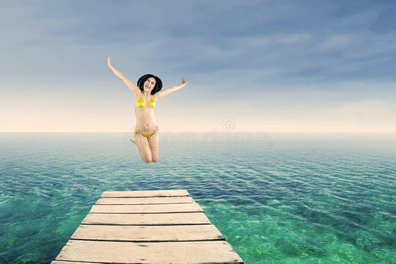 Mujer feliz que salta en el embarcadero fotografía de archivo