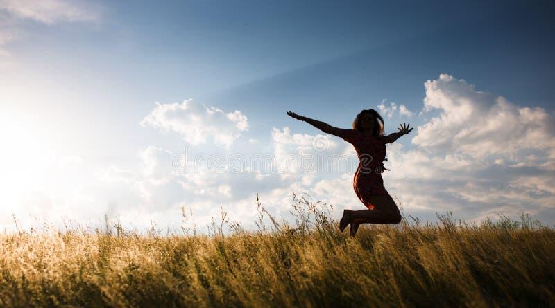 Mujer feliz que salta en el prado imagen de archivo libre de regalías