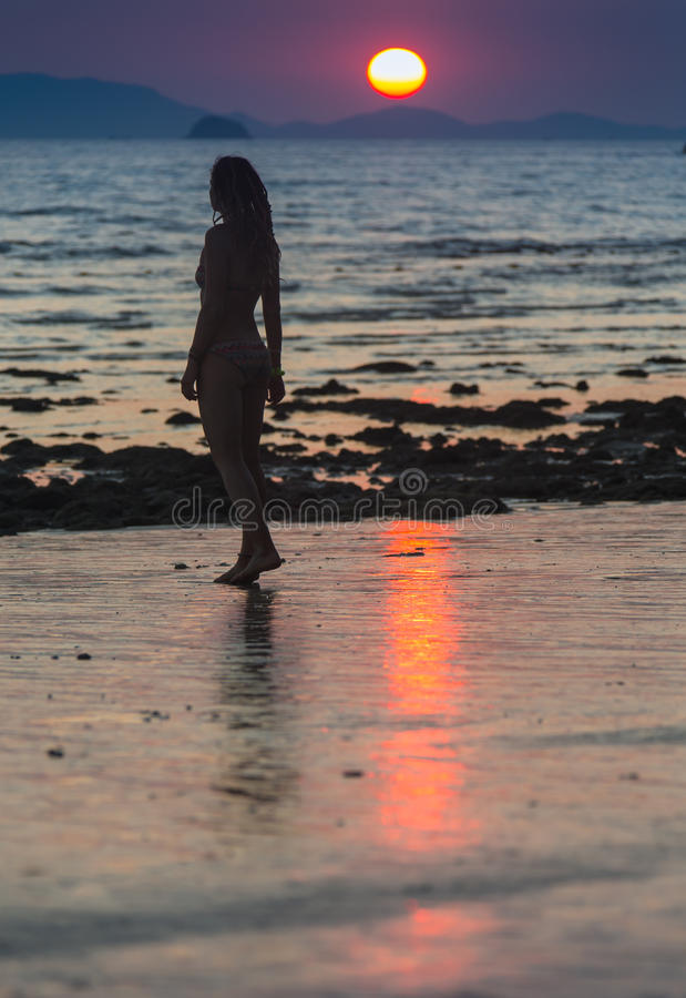 Mujer feliz que salta en puesta del sol del mar fotografía de archivo