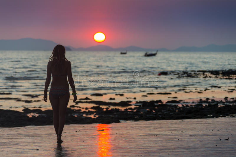 Mujer feliz que salta en puesta del sol del mar imágenes de archivo libres de regalías