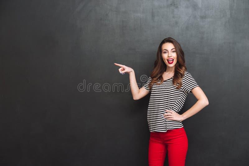Mujer feliz que señala lejos y que sostiene el brazo en la cadera imagen de archivo libre de regalías