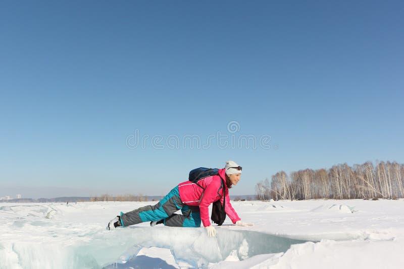 Mujer feliz que se arrastra en una masa de hielo flotante de hielo en un río congelado fotografía de archivo libre de regalías