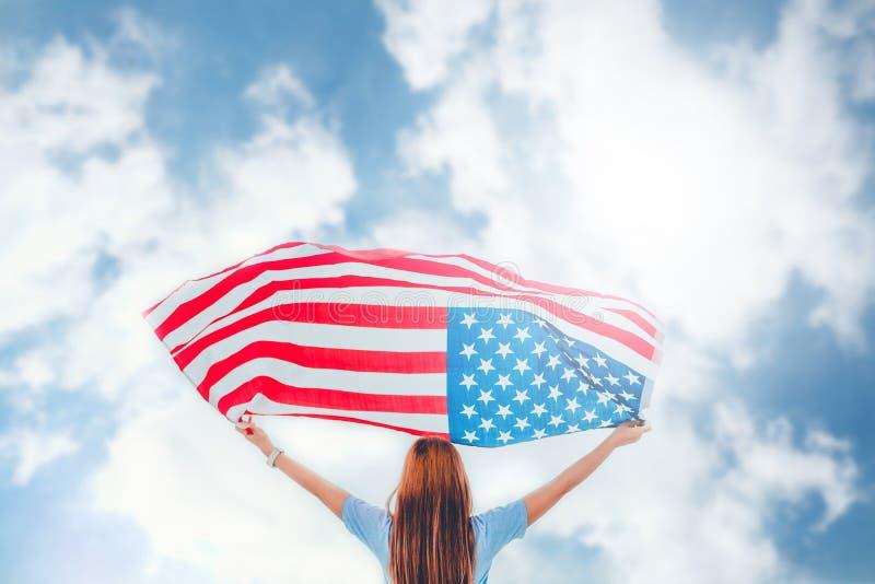 Mujer feliz que se coloca con día de fiesta patriótico de la bandera americana Ce de los E.E.U.U. fotografía de archivo libre de regalías