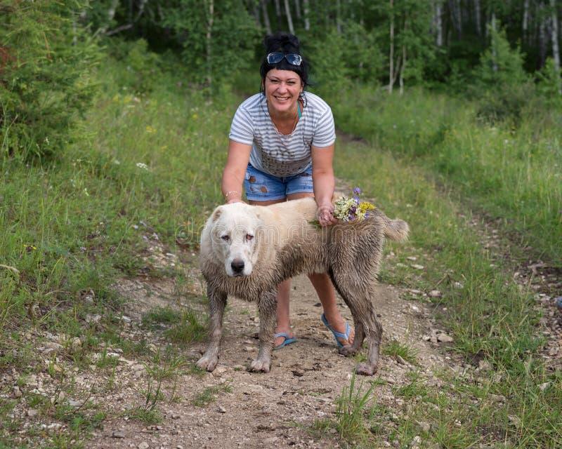 Mujer feliz que se coloca con el perro mugriento en el bosque fotos de archivo
