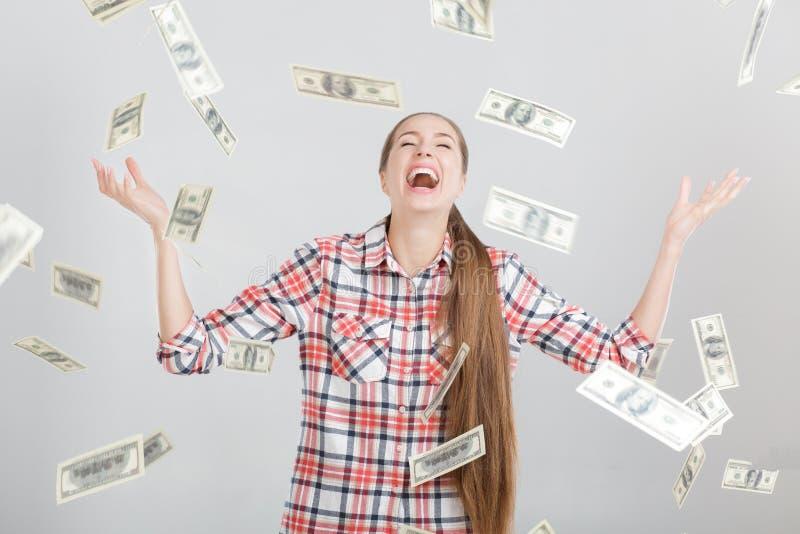 Mujer feliz que se coloca debajo de la lluvia del dinero fotos de archivo
