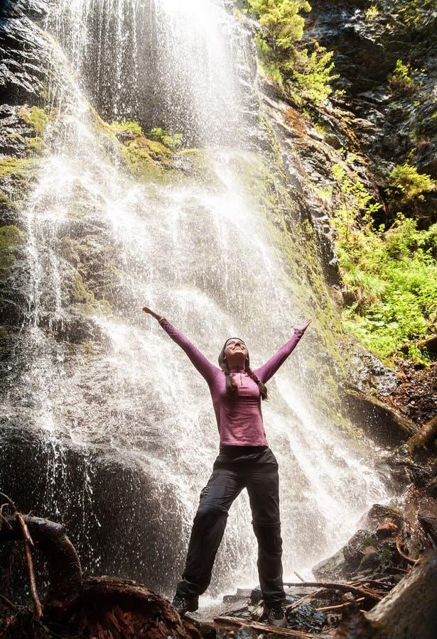 Mujer feliz que se coloca delante de la cascada fotos de archivo