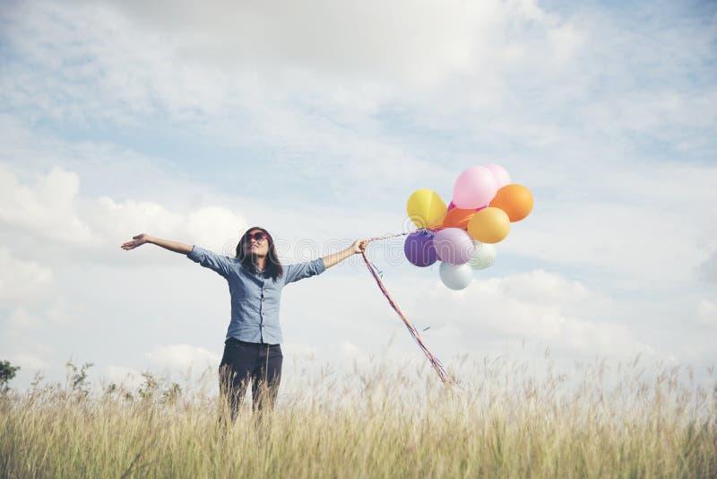 Mujer feliz que se considera colorida de globos en un prado verde con el cielo azul nublado imagenes de archivo