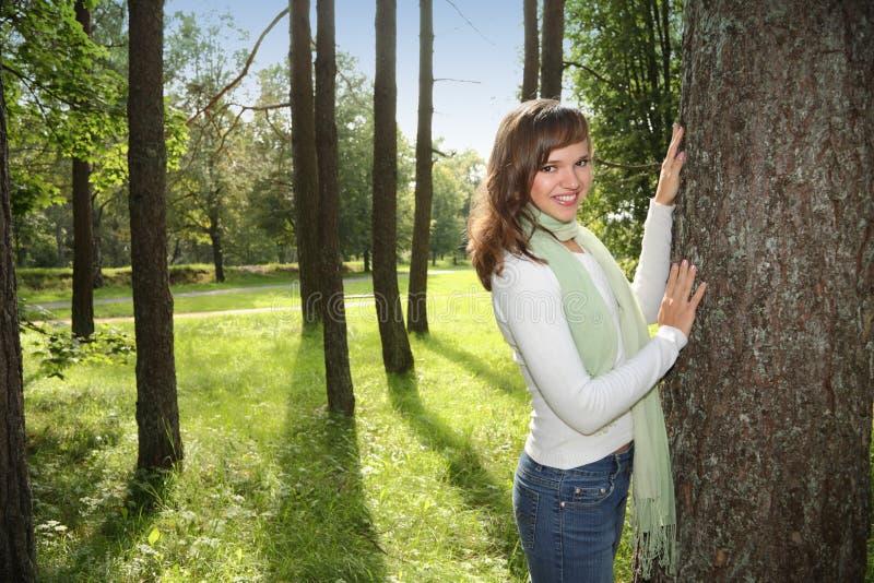 Mujer feliz que se inclina en árbol imagenes de archivo