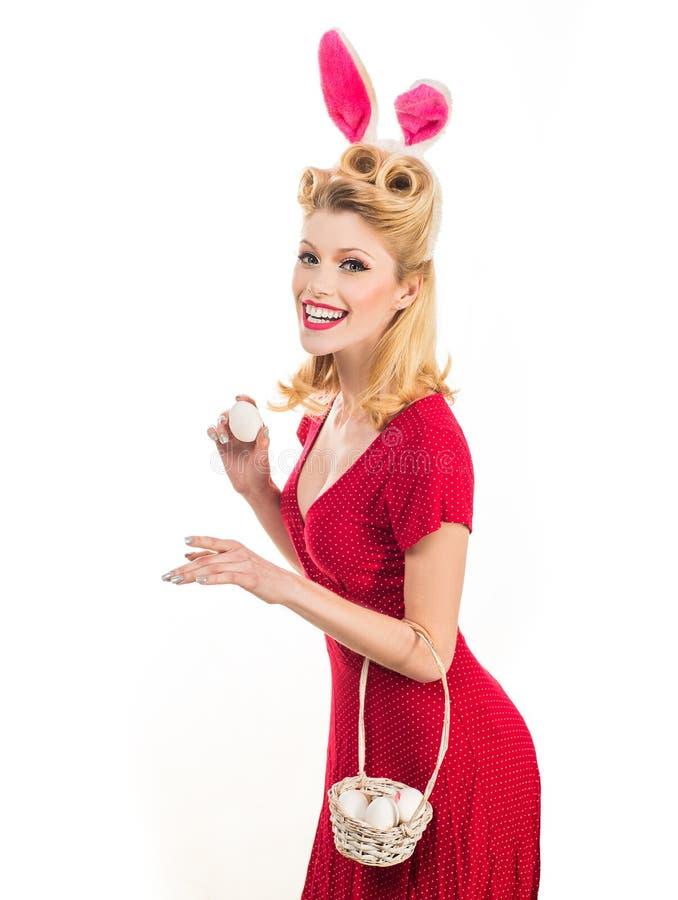 Mujer feliz que se prepara para Pascua Muchacha rubia hermosa con los oídos del conejito y el huevo de Pascua Cazas bonitas de la imagenes de archivo