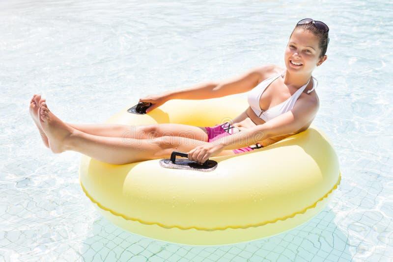 Mujer feliz que se relaja en el tubo interno en piscina foto de archivo libre de regalías