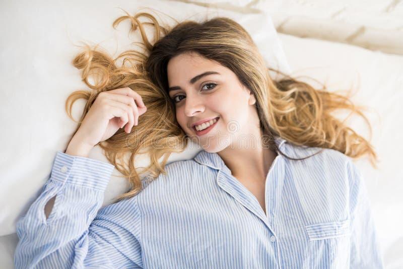 Mujer feliz que se relaja en su cama fotos de archivo