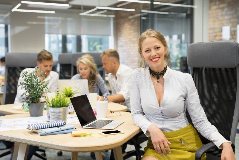 Mujer feliz que se sienta con los compañeros de trabajo foto de archivo