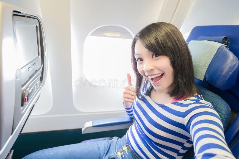 Mujer feliz que se sienta en aeroplano imágenes de archivo libres de regalías