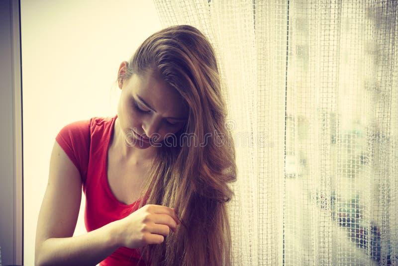 Mujer feliz que se sienta en el alféizar, mañana de activación imagen de archivo libre de regalías