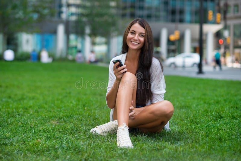 Mujer feliz que se sienta en hierba verde en el parque de la ciudad y que usa smartphone imagenes de archivo