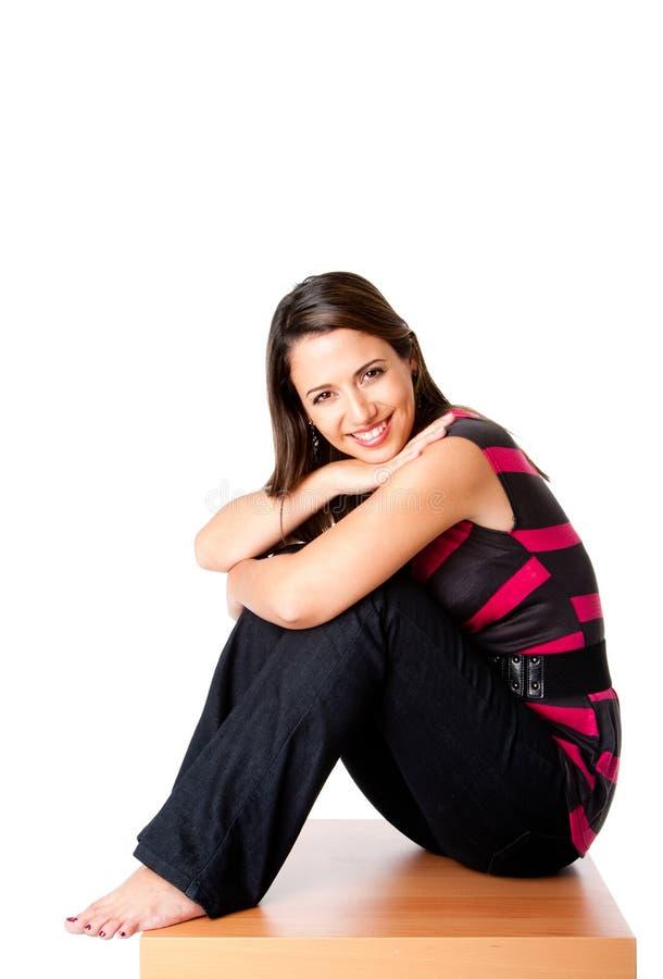 Mujer feliz que se sienta en la madera foto de archivo libre de regalías