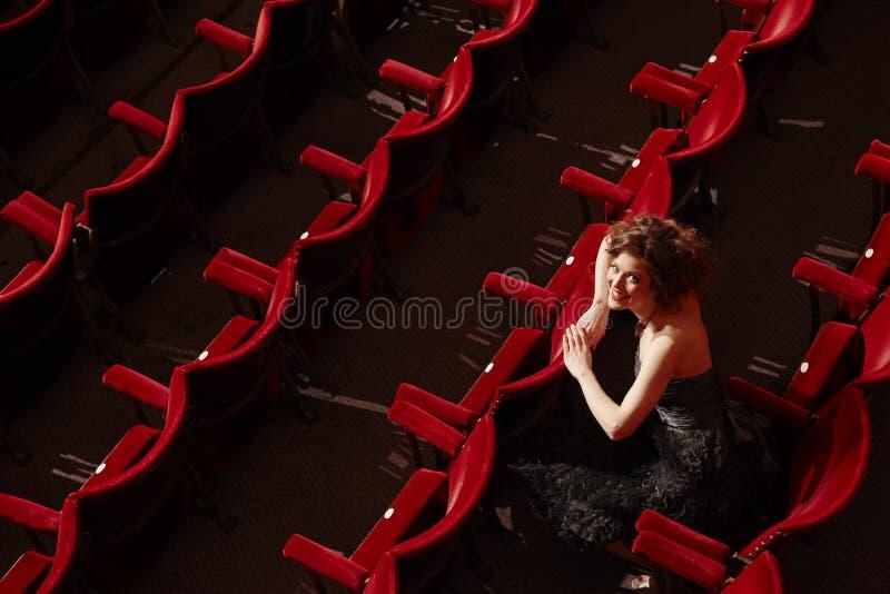 Mujer feliz que se sienta en parada del teatro imagen de archivo libre de regalías