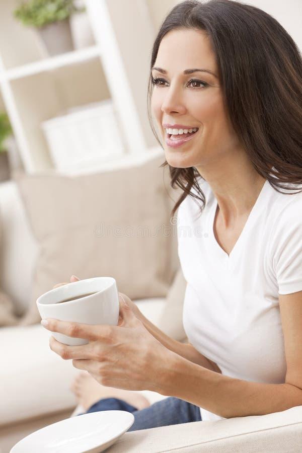 Mujer feliz que se sienta en té o café de consumición del sofá fotografía de archivo libre de regalías