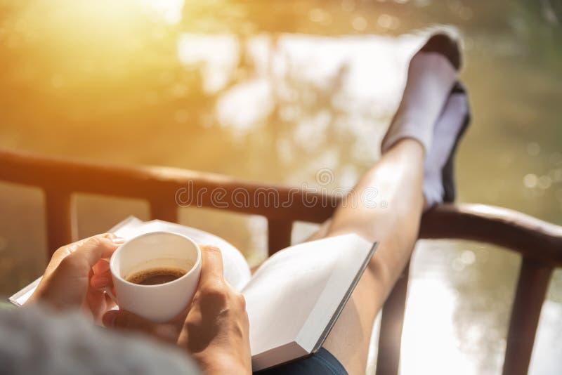 Mujer feliz que sienta y que sostiene la taza de café caliente fotos de archivo
