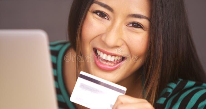 Mujer feliz que sonríe con la tarjeta a disposición foto de archivo libre de regalías
