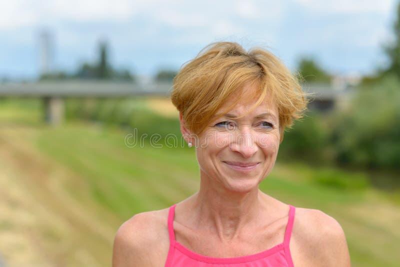 Mujer feliz que sonríe a sí misma como ella mira fotos de archivo libres de regalías