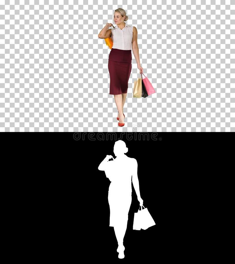 Mujer feliz que sostiene bolsos de compras, sonriendo y caminando, Alpha Channel fotografía de archivo libre de regalías