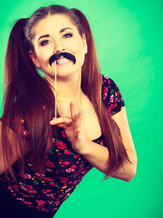 Mujer feliz que sostiene el bigote falso en el palillo foto de archivo libre de regalías