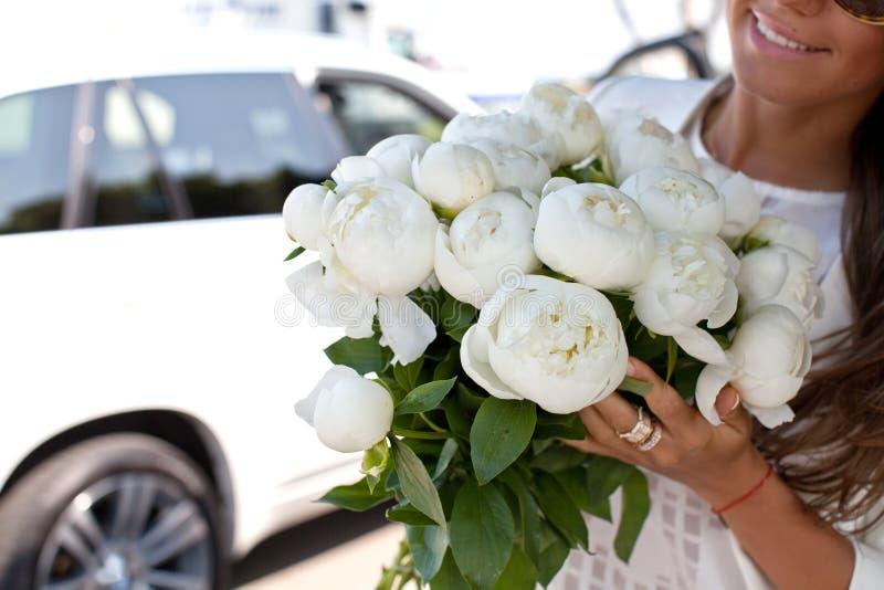 Mujer feliz que sostiene el ramo hermoso de peonías blancas en manos imagen de archivo