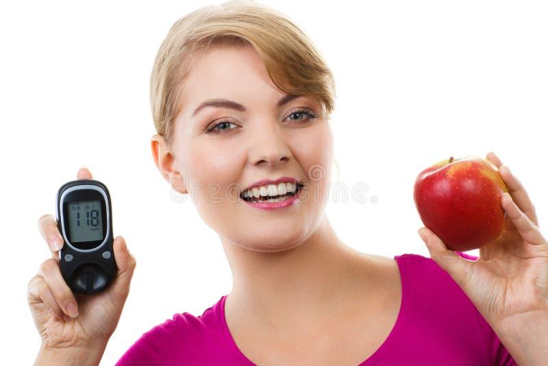 Mujer feliz que sostiene glucometer y la manzana fresca, midiendo y comprobando el nivel del azúcar, concepto de diabetes imágenes de archivo libres de regalías