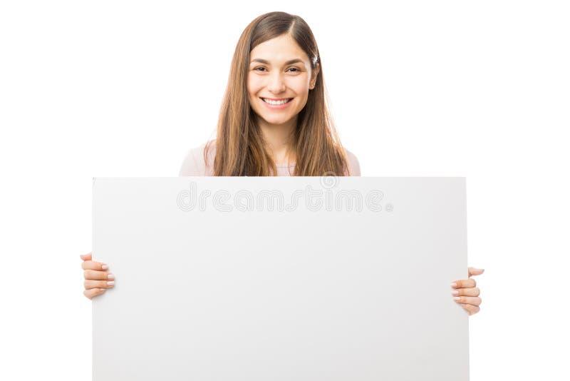 Mujer feliz que sostiene la cartelera en blanco sobre el fondo blanco imágenes de archivo libres de regalías