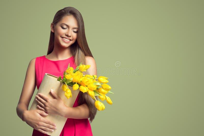 mujer feliz que sostiene la cesta con los tulipanes amarillos foto de archivo libre de regalías