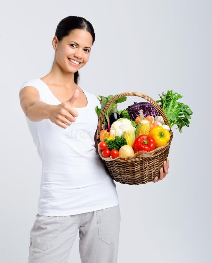 Mujer feliz que sostiene la cesta de verduras crudas imagen de archivo libre de regalías