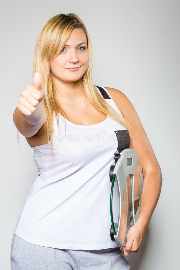 Mujer feliz que sostiene la máquina del peso que muestra el pulgar para arriba fotografía de archivo