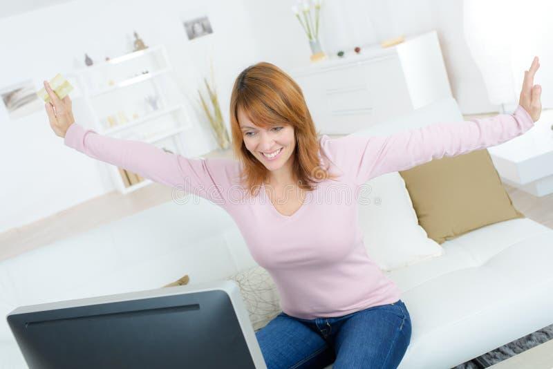 Mujer feliz que sostiene la tarjeta de banco y que mira la pantalla de ordenador foto de archivo libre de regalías