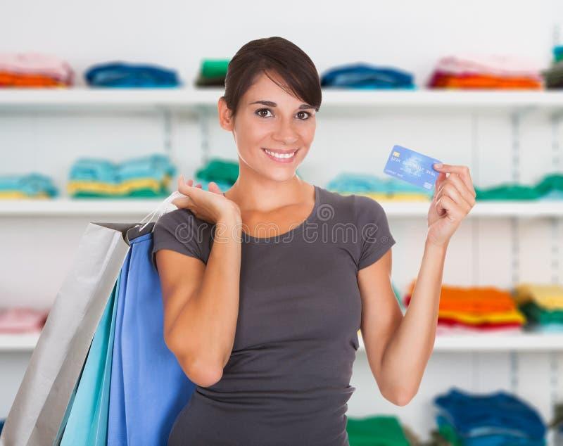 Mujer feliz que sostiene la tarjeta de crédito en tienda de ropa foto de archivo