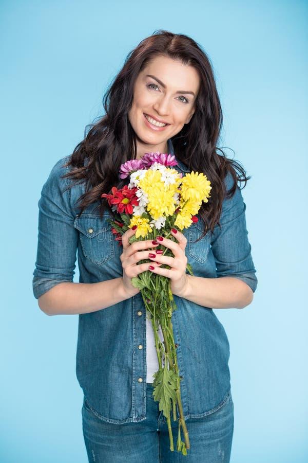 Mujer feliz que sostiene las flores en estudio en azul fotografía de archivo