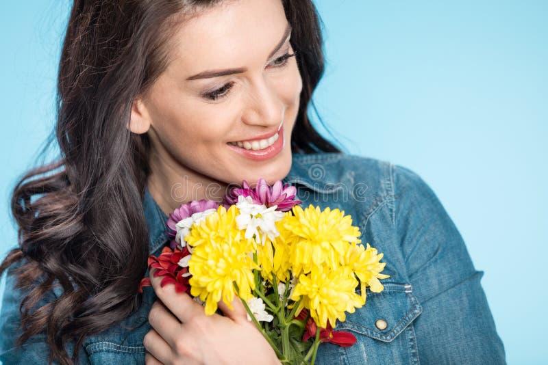 Mujer feliz que sostiene las flores en estudio en azul imagen de archivo libre de regalías
