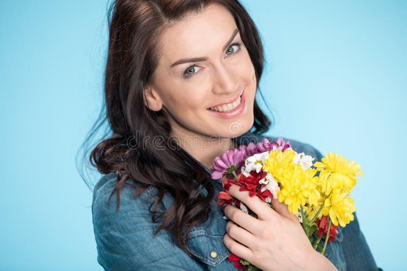 Mujer feliz que sostiene las flores en estudio en azul fotos de archivo libres de regalías