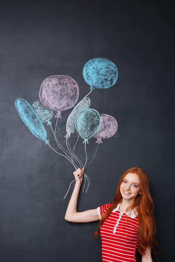 Mujer feliz que sostiene los globos dibujados en fondo de la pizarra foto de archivo